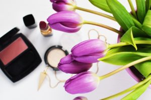 makeup among tulips on desk
